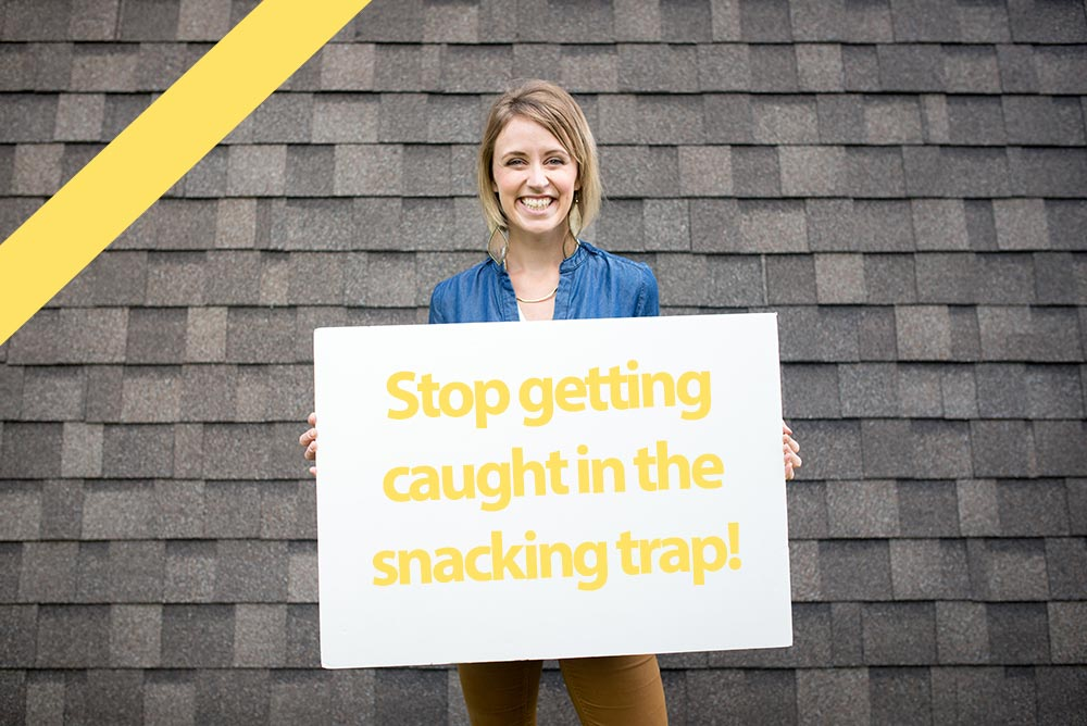 """Jessica holding sign that says """"stop getting caught in the snacking trap!"""""""